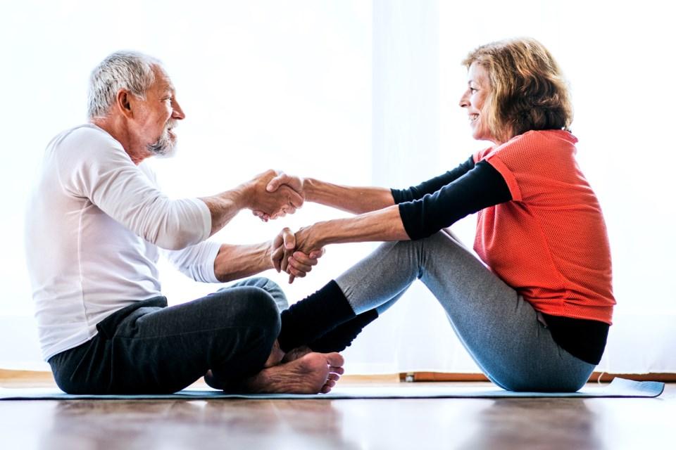 a-senior-couple-doing-exercise-at-home-JYWPMDV