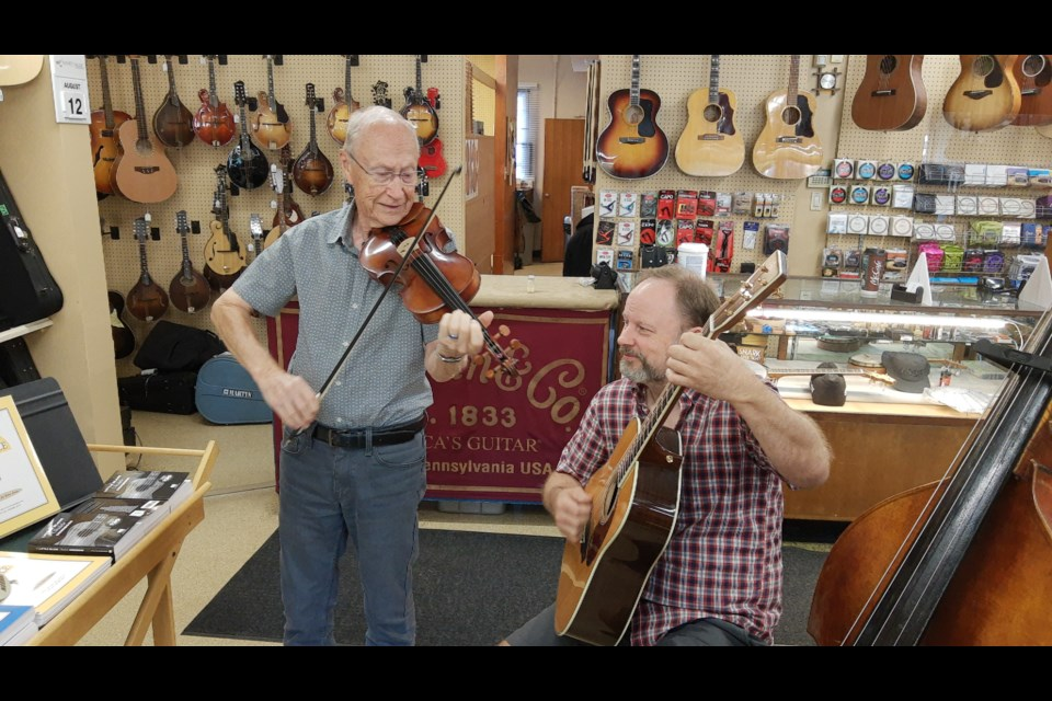 Alfie Myhre (left) and son Byron Myhre playa Bluegrass standard, Down YonderatMyhre's Music on Edmonton's 118th Avenue. Photo: Terry Jorden.