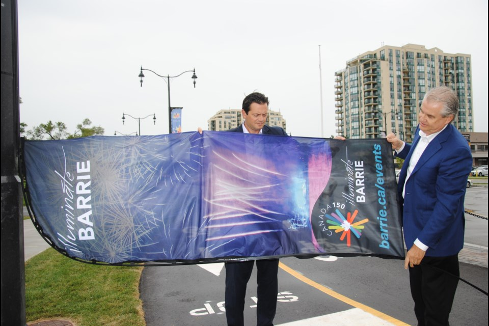 Mayor Jeff Lehman and The Look Company CEO Ed Burke unfurl the banner that's to go up near Centennial Beach.