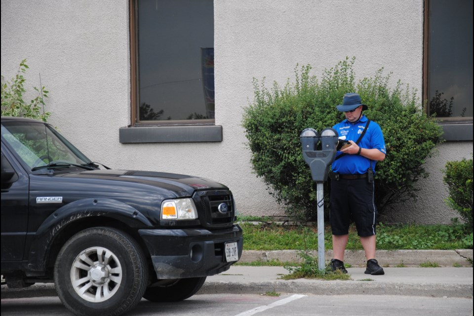 A Barrie parking enforcement officer continues his duties as crowds gather nearby for the moving of the cenotaph.