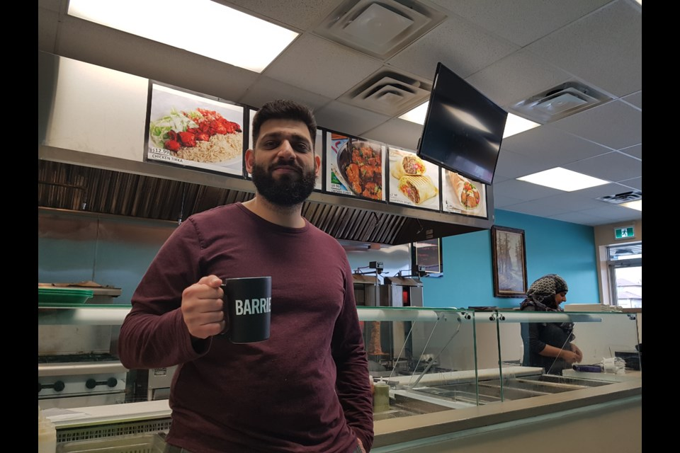Kashif Shahzad enjoys a BarrieToday mug while his wife, Wazhma Barez, serves up the lunchtime crowd. Shawn Gibson for BarrieToday