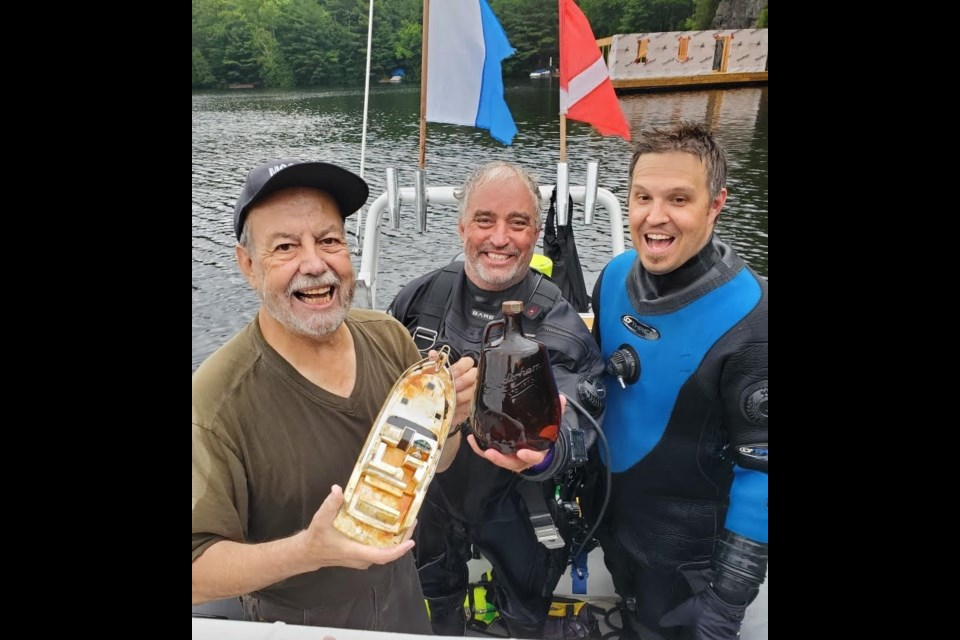 Dieter Mueller, Dave Davison and Adam Blokzyl, are ecstatic that the hunt for the lost case of whisky on Otter Lake ended in success.