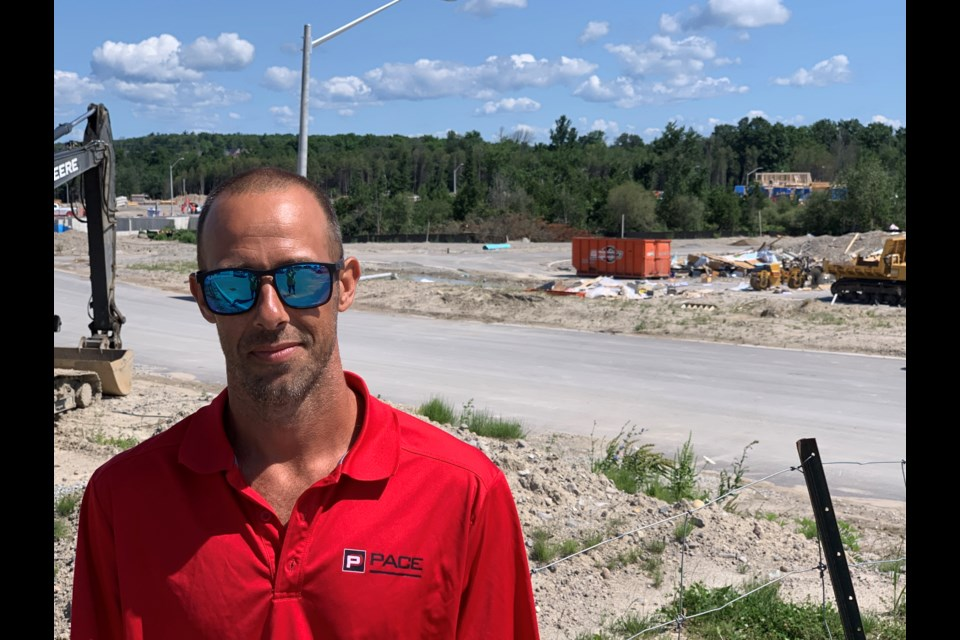 Stephen Galyen stands in front of the debris left after the construction trailer he and two colleagues were inside was destroyed in the July 15 tornado in south-end Barrie.