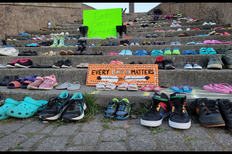 Signs are laid out and children's shoes line the steps of the Spirit Catcher in downtown Barrie in memory of the the 215 children whose bodies were found buried on the grounds of a residential school in Kamloops, B.C.