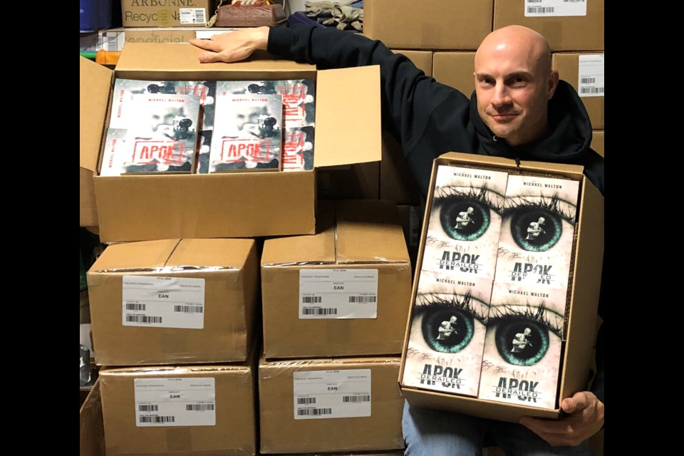 Michael Walton stands with the many books of his new APOK Derailed, which is set to be released on Thursday Oct.09, 2019. Photo by Stephanie Piette