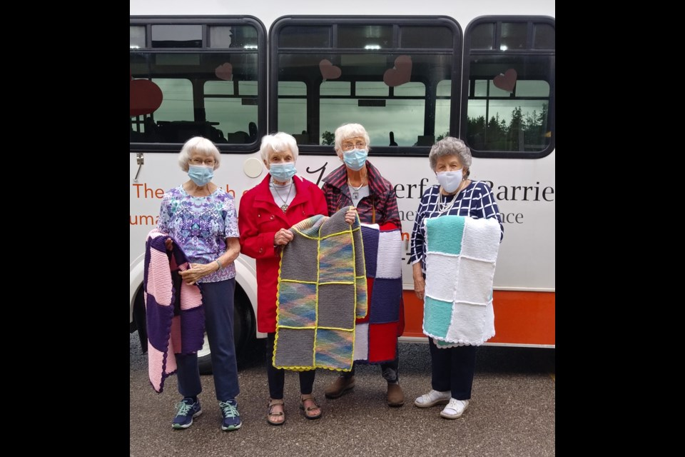 Betty Franklin, Elsie McGuire, Janet Powell and Jeanneke VanWesenbeeck, members of the knitting group at Waterford Barrie Retirement Residence, showcase four of the afghans they generously donated and delivered to Hospice Simcoe. Supplied photo