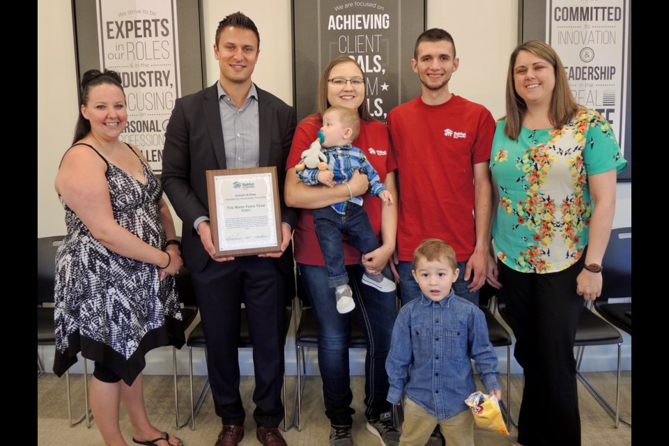 CEO Mark Faris is pictured with Habitat for Humanity home recipient Michelle Steele, future home owners Chelsea and Terry Pagliei and their two sons and Family & Volunteer Services Coordinator Jennifer Berry.