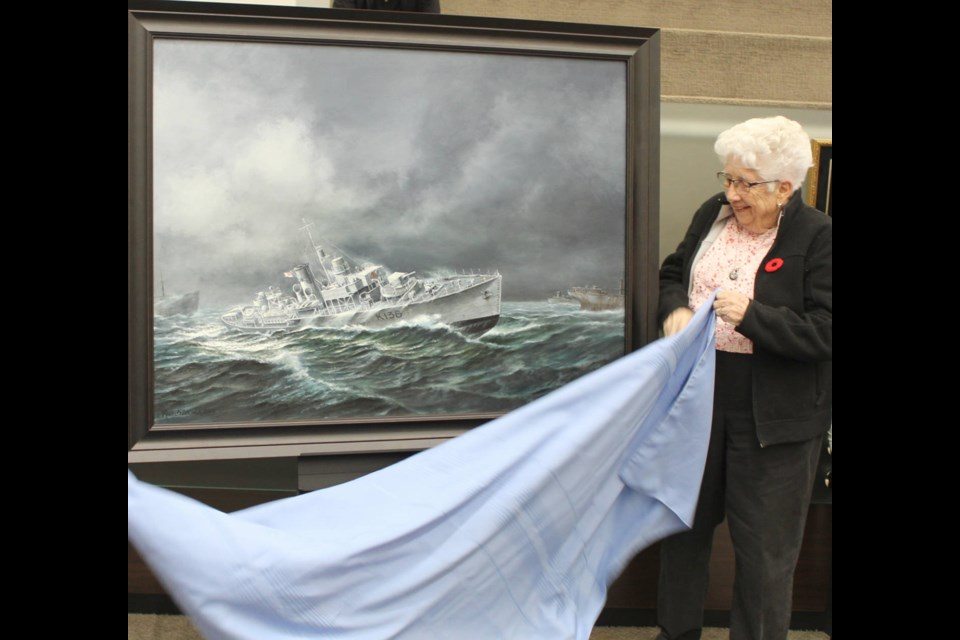 Former Barrie mayor Janice Laking, one of the donors to the Sir Robert Barrie Project, unveils a painting of HMCS Barrie at Monday's council meeting at Barrie City Hall. Raymond Bowe/BarrieToday