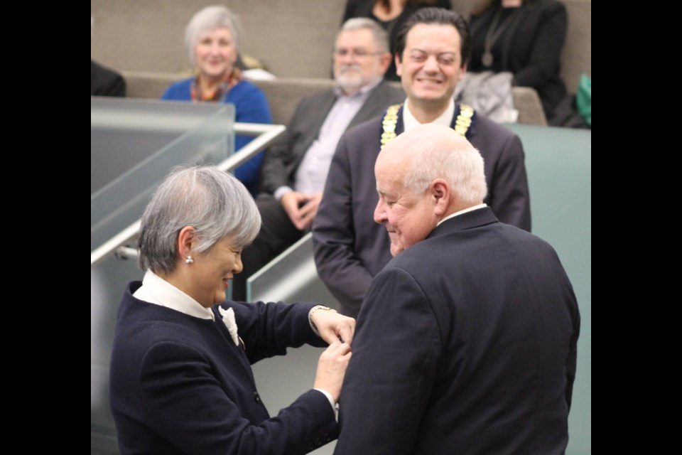 Takako Ito,consul-general of Japan in Toronto, presents Dave Morrison with a special pin after he was honoured with the Order of the Rising Sun, Gold and Silver Rays at Barrie city council on Monday, Jan. 13, 2020, as Barrie Mayor Jeff Lehman looks on. Raymond Bowe/BarrieToday