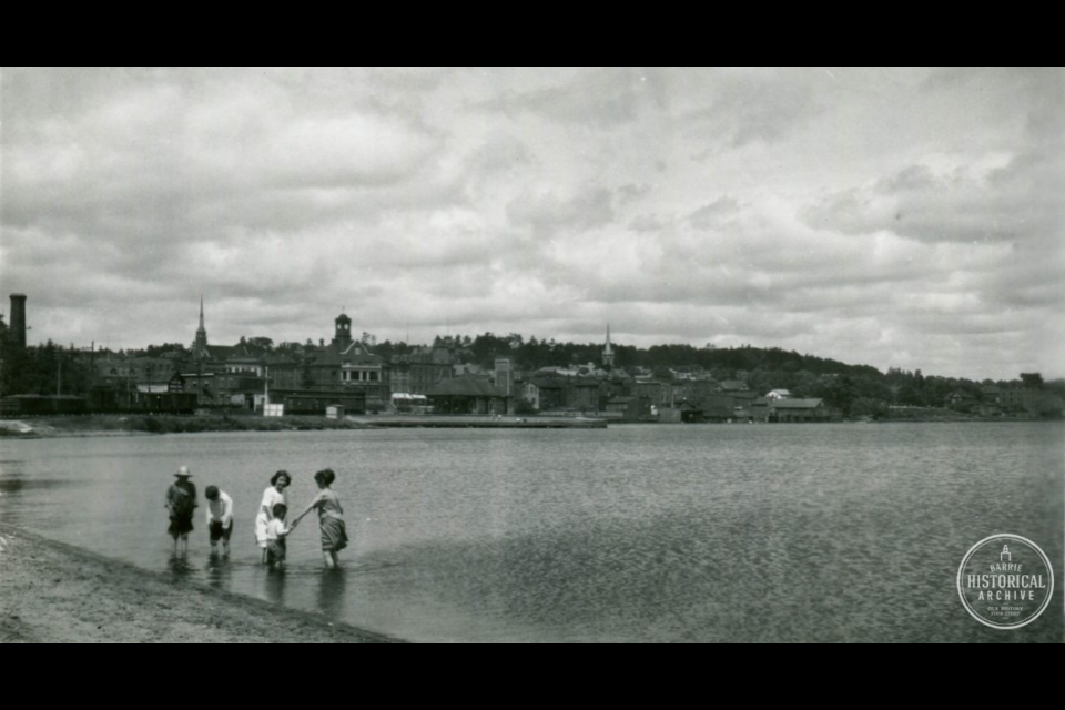 The waters of Kempenfelt Bay look calm as a family enjoys the old bathing beach near the foot of Mary Street circa 1945.