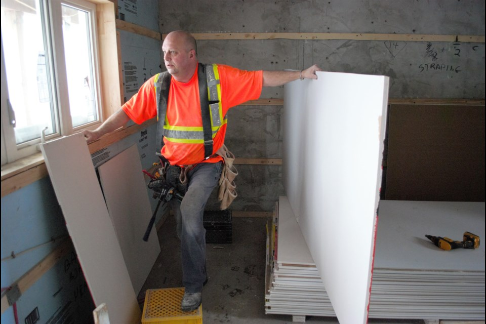 Matt Macpherson prepares drywall for installation in one of the bachelor-sized units at Lucy's Place. Jessica Owen/BarrieToday