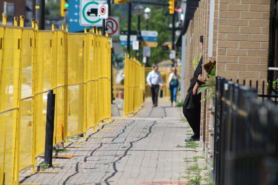 Pedestrians can still make their way to businesses along Dunlop Street East, as construction barriers went up on Aug. 20, 2019. Shown is near the intersection of Mulcaster Street. Raymond Bowe/BarrieToday