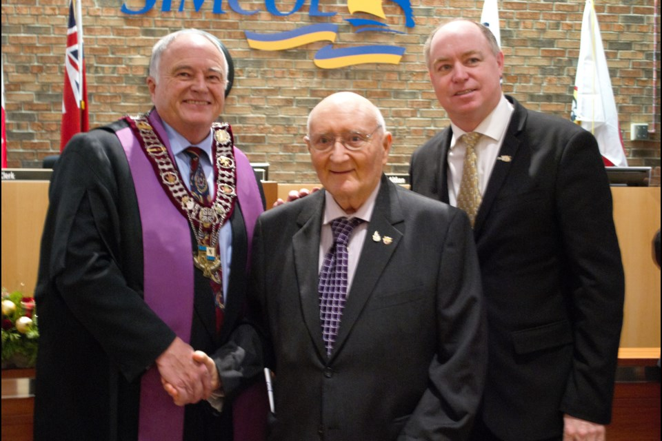 From left, Warden George Cornell shakes hands with former warden Ross Hastings while former deputy warden Terry Dowdall looks on. Jessica Owen/Village Media