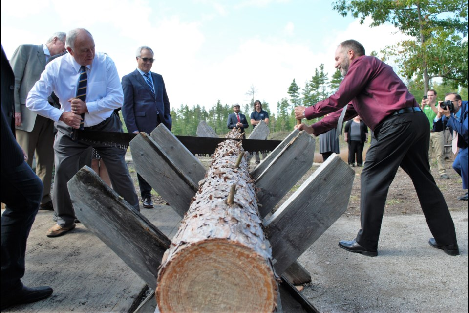 Simcoe County Warden George Cornell and county forester Graeme Davis cut the log (instead of cutting the ribbon), signalling the opening of The Red Pine House, a forestry education centre on the Simcoe County Museum property. Jessica Owen/BarrieToday