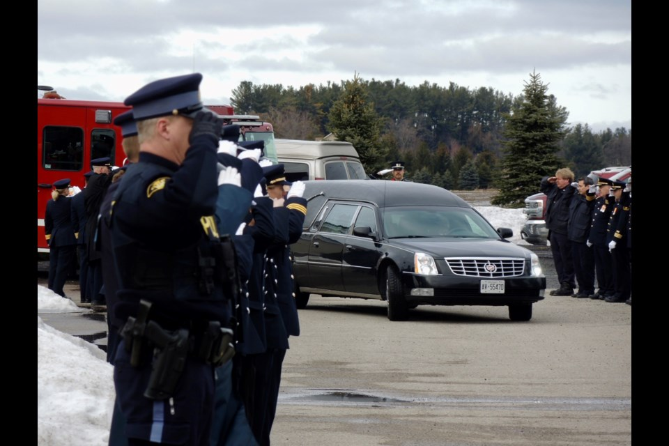 Mourners salute Terry 'Weapon' Weatherup following his funeral service in Baxter.  