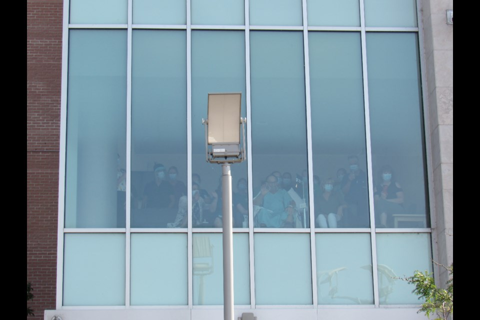 Grant McCulloch is surrounded by family as he watches the parade go by his RVH window, Monday, July 26, 2021