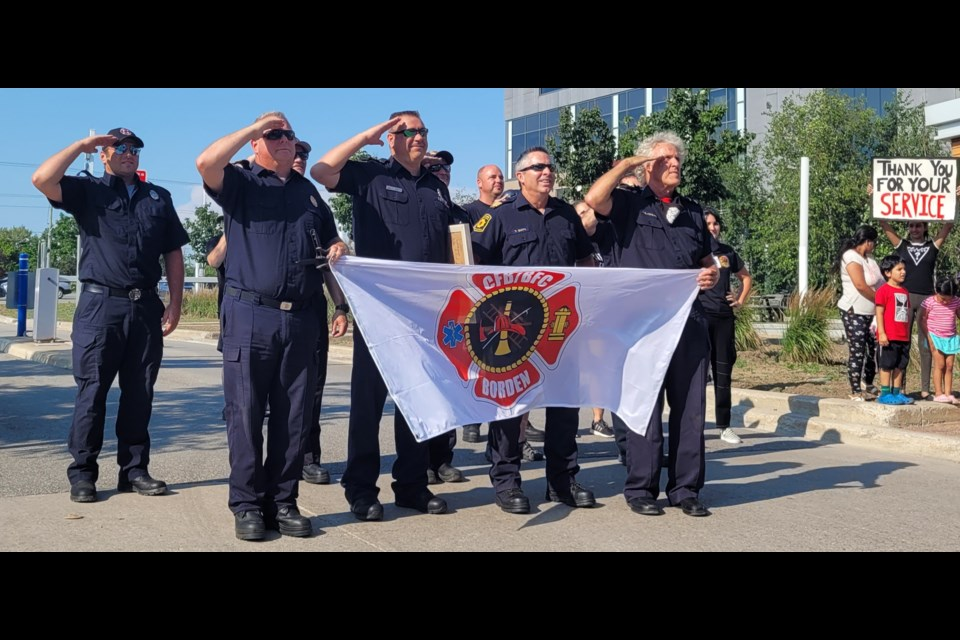 First-responders salute Grant McCulloch at Monday's parade for the retired firefighter. McCulloch passed away from cancer on Wednesday, July 28, 2021.