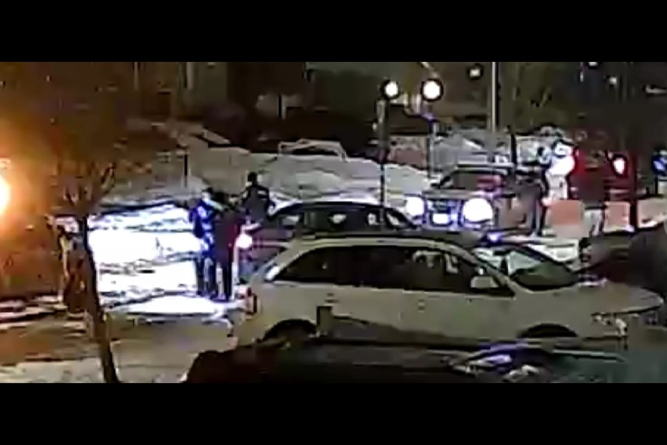 In this grainy surveillance image from the area, Barrie police search for evidence following a stabbing on Harrogate Crescent, Tuesday evening, that left a teen with serious injuries.