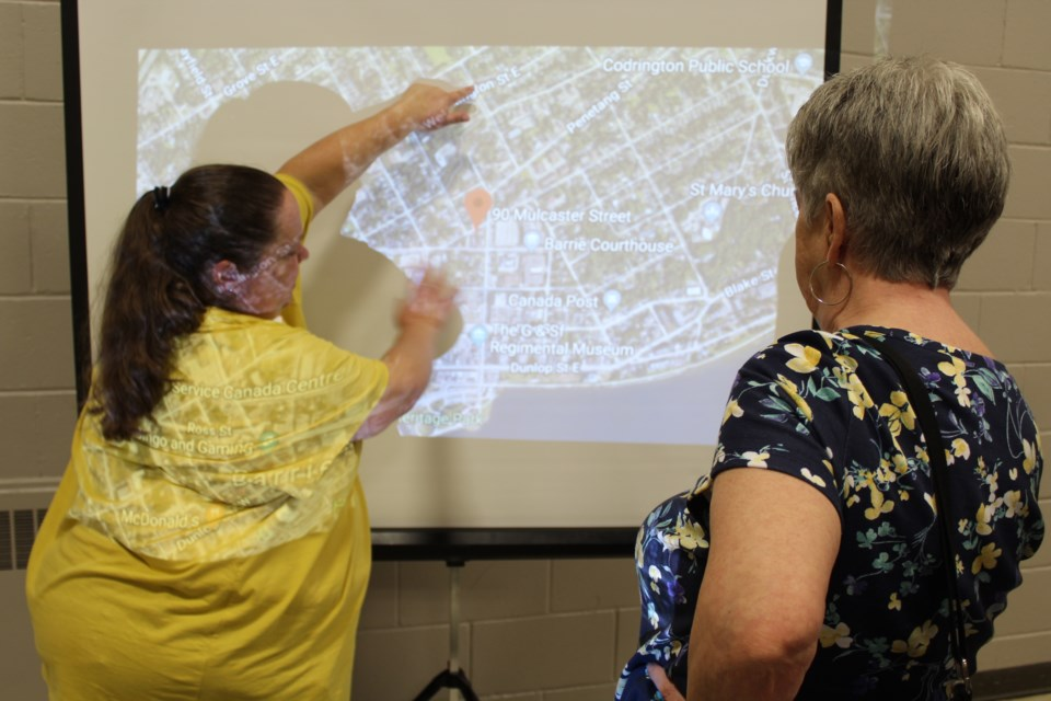 An official from the Canadian Mental Health Association (left) explains the preferred location for a proposed supervised consumption site in downtown Barrie during a drop-in meeting on May 15, 2019 at Collier Street United Church. Raymond Bowe/BarrieToday