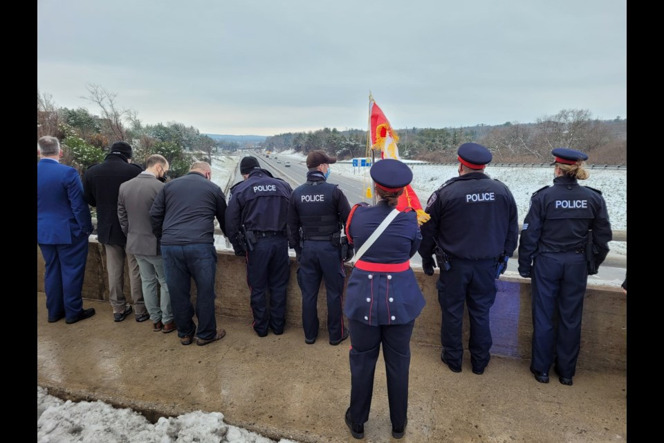 Local police officers pay her respects to fallen OPP Const. Marc Hovingh, Monday at the Bayfield Street bridge over Highway 400. Shawn Gibson/BarrieToday