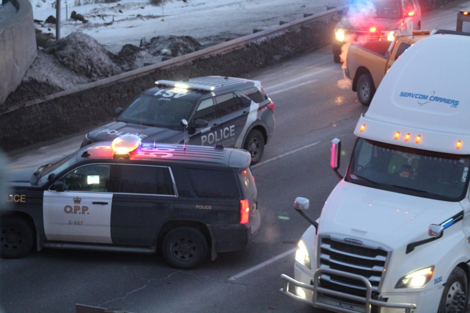 Police investigate in the northbound lanes of Highway 400 after a pedestrian fell from the Anne Street bridge, Thursday night.