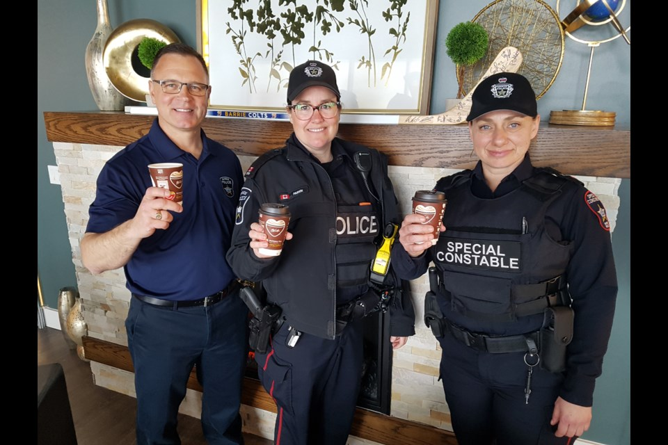 From left, Barrie police communications co-ordinator Peter Leon, Const. Jackie Parkin, Special Const. Shannon Calladine raise a coffee and give cheers to National Police Week, on May 12, 2019. Shawn Gibson/BarrieToday