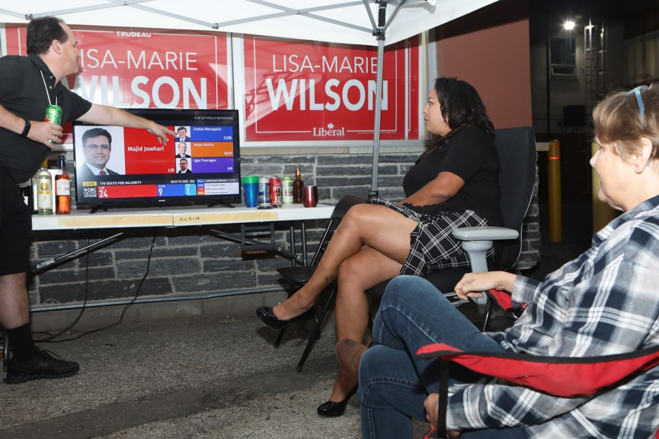 Lisa-Marie Wilson (middle), the Liberal candidate in Barrie-Innisfil, watches the federal election results come in with her supporters, Monday night.
