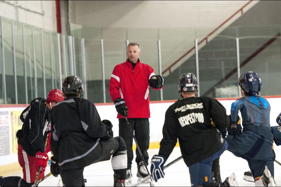 Paul Matheson provides skating instruction to a group of hockey players. Image supplied