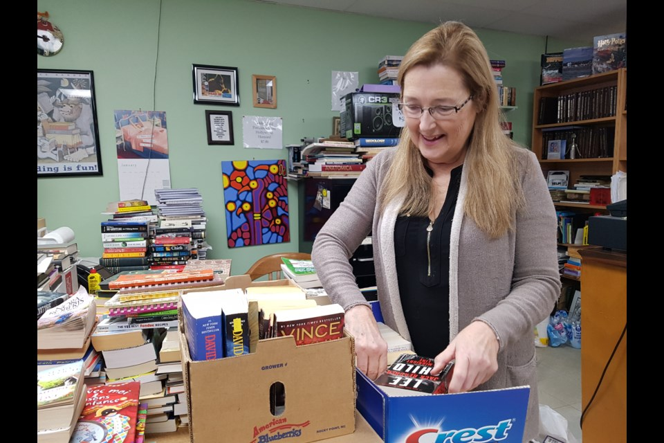 Wendy Cahill looks over some of the many books she gets everyday  from people looking to sell, Wednesday Jan. 15, 2020. Shawn Gibson/BarrieToday