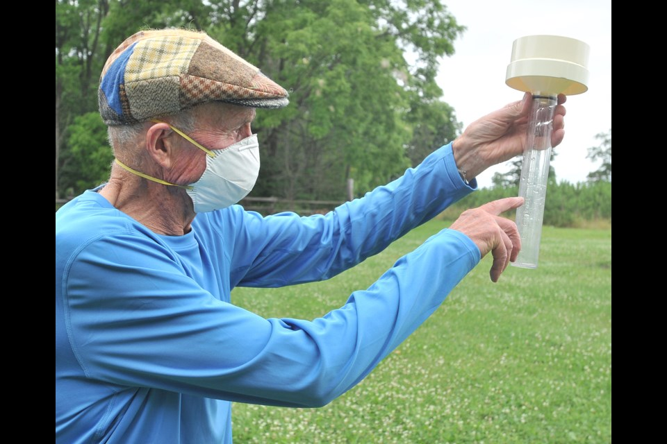 John Dunsmore checks out a rain gauge at his Shanty Bay farm just outside of Barrie earlier this week. Nearly four inches of rain fell in the area on Sunday, much to the chagrin of long-weekend campers. Ian McInroy for BarrieToday