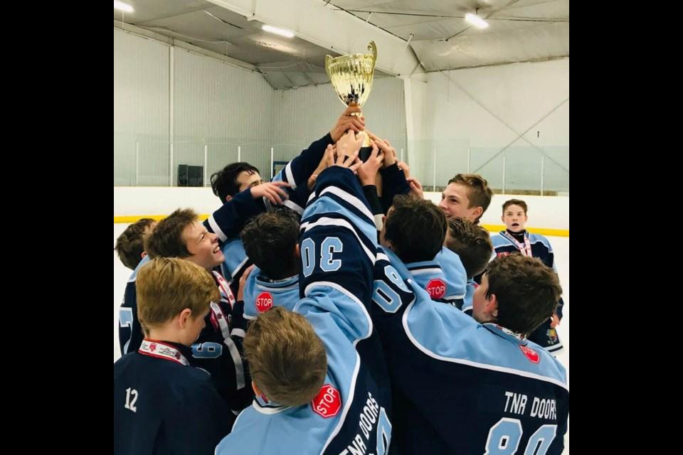 Barrie minor hockey players hoist the TNR Doors Trophy. Image supplied
