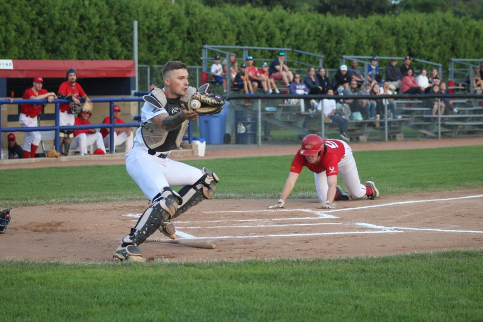 Barrie Baycats catcher Jake MacDonald tries to make a play at home plate during Intercounty Baseball League action against the Hamilton Cardinals on Thursday, July 22, 2021, at Coates Stadium in Midhurst.