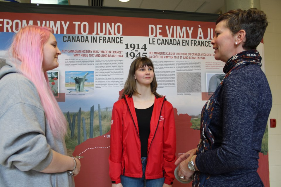 Bear Creek Secondary School students Ricki Harris, left, and Jadyn Powell speak with history teacher Christa Culhane on Thursday at the Barrie high school. Raymond Bowe/Barrie Today