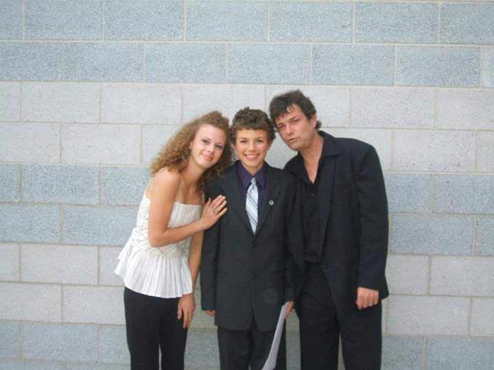 Nickolas Pasowisty is in the centre of the photo taken at his Grade 8 graduation. He is shown with his dad, James, and sister, Tracy.