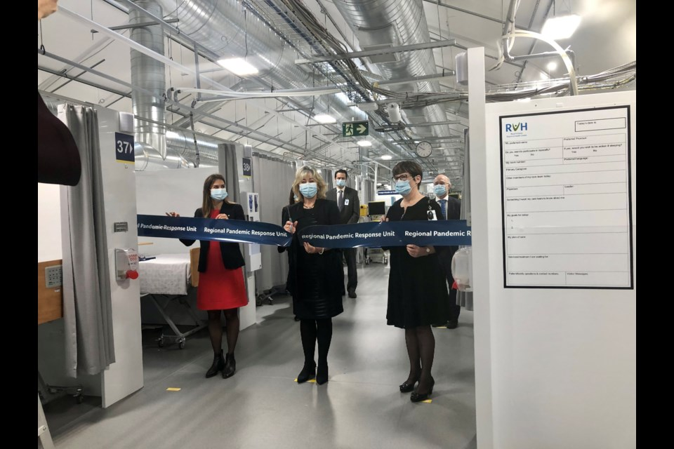 Barrie-Innisfil MPP Andrea Khanjin, RVH Chair Charlotte Wallis, centre, and RVH CEO Janice Skot, right, cut the ribbon during the official opening of the Regional Pandemic Response Unit in the parking lot of the Barrie hospital.