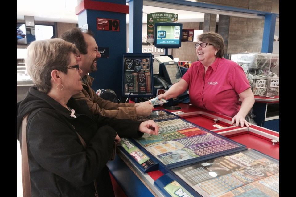Wingate Lottery owner Cathy Strawn shares a joke with customers. April 30th is her last day on the job. She blames the  minimum wage increase for putting her out of business after 29 years.