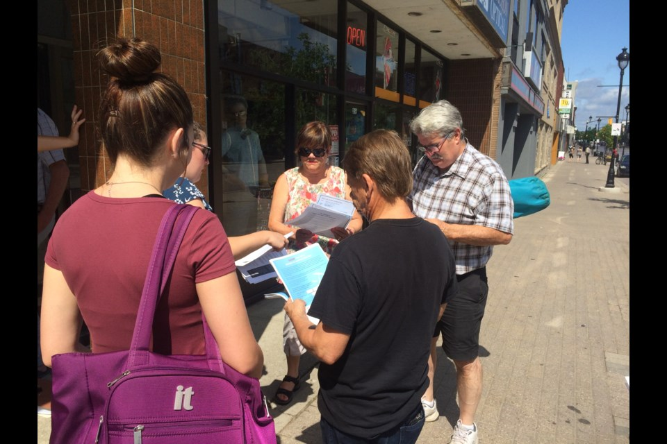 Small group gathered outside Nipissing MPP Vic Fedeli's constituency office supporting legal clinic's Day of Action