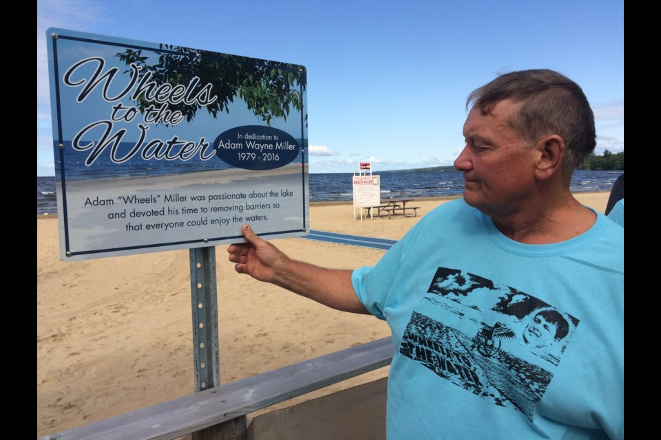 "North Bay's first beach accessibility mat was dedicated in honour of Adam ""Wheels"" Miller who worked tirelessly to get a mat for North Bay. His father Wayne gently touches the sign which bears his son's name, located beside the mat at Marathon Beach."