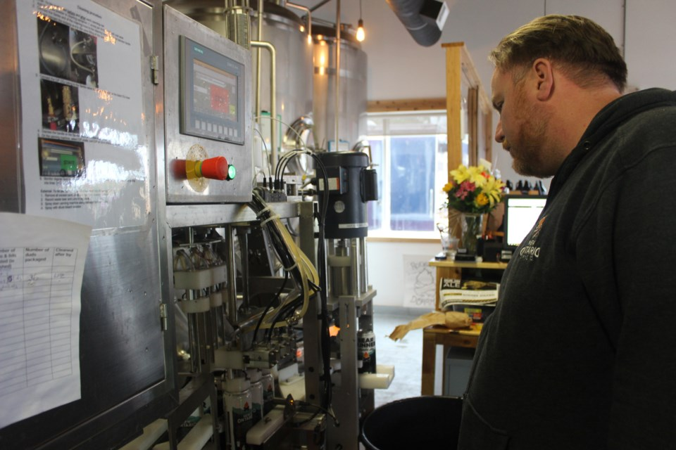 Co-owner Mike Harrison inspects the new canning machine, which will help them increase can production as New Ontario Brewing expands its products. Photo by Ryen Veldhuis.