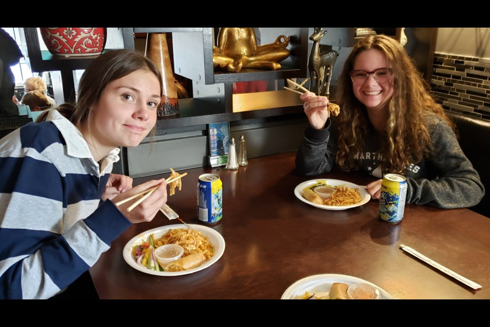 Emma Walters and Aili Smith at Dave's Green Papaya trying chopsticks. Supplied.