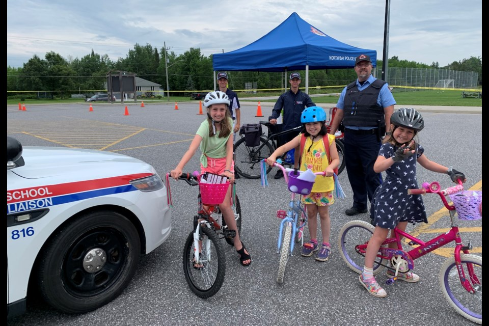 The North Bay Police Service Bike Rodeo is back. Front row Hazel Craig, Amelie Voyer and Evelyn Craig, Back row  Brandon Mills, Jacob Leveille, Special Constable John Schultz.