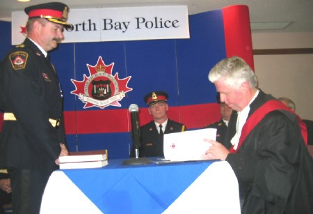 Justice Roland Harris, a former North Bay Crown attorney, swore in Paul Cook as chief and Al Williams as deputy chief of the North Bay police service.