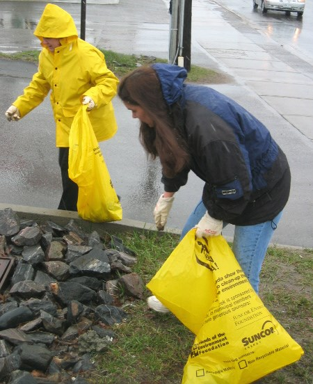 Two volunteers scour for litter on Trout Lake Road today, as part of Community Clean-up Day.