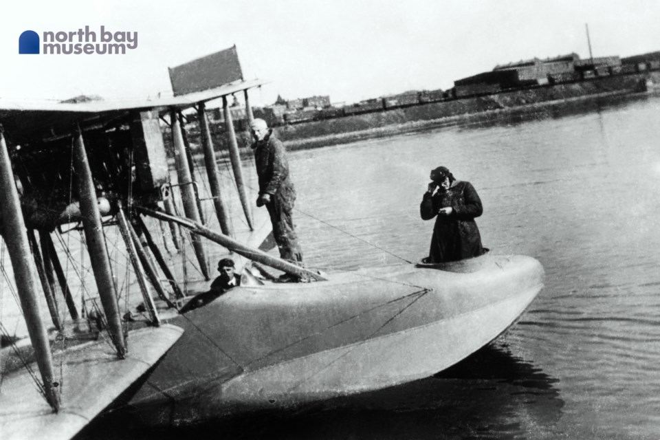 An HS-2L flying boat on Lake Nipissing in the summer of 1922. Visible behind the aircraft and its crew is North Bay's downtown and the CPR rail yards.