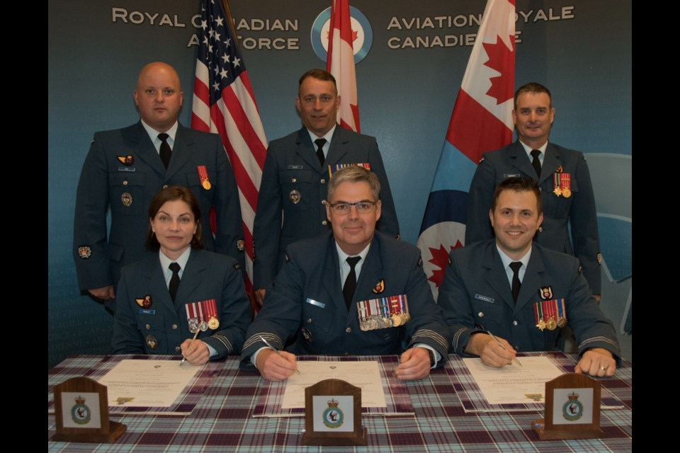 (Front Row) The In-coming Commander, Major Brenda Tinsley (left), Out-going Commander, Major Shawn Guilbault (right) and Presiding Officer, Colonel Henrik Smith (centre) at the official signing ceremony. (Rear Row) Master Warrant Officer Charles Rice, Chief Warrant Officer John Short, and Master Warrant Officer Jamie Rideout.                                                                                                                                                                                                                        Image by: Corporal Joseph Morin.
