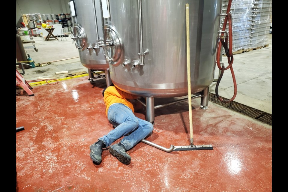 A New Ontario Brewing Company worker installs critical equipment for the making of hand sanitizer In North Bay. (Supplied photo)