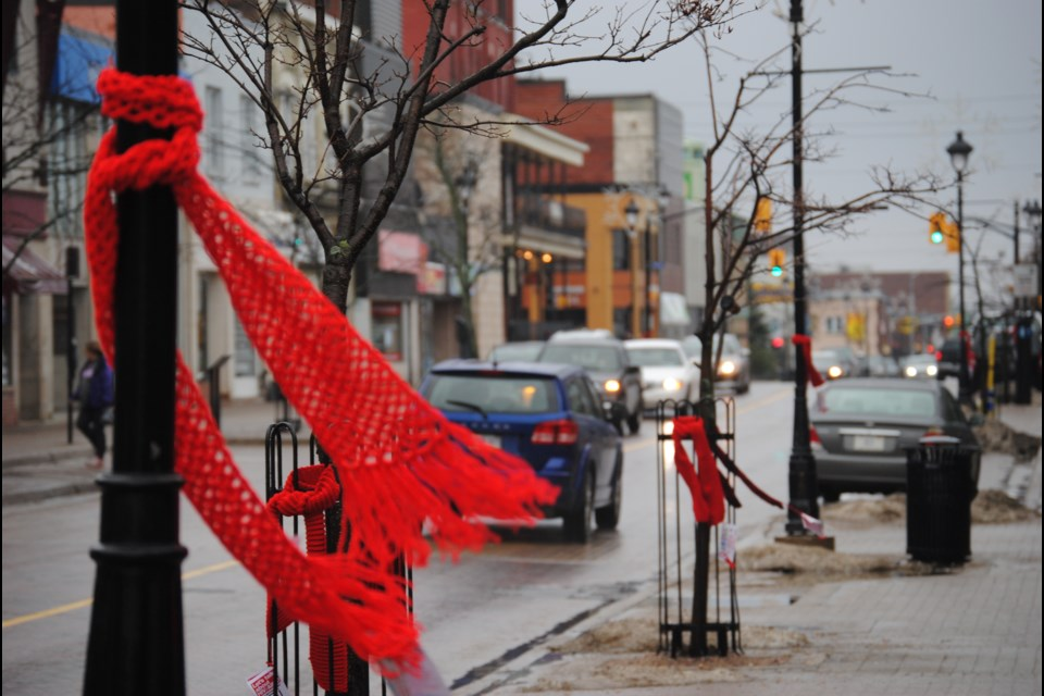 Red scarves used to promote AIDS awareness flutter in the breeze downtown North Bay. Photo by Stu Campaigne.