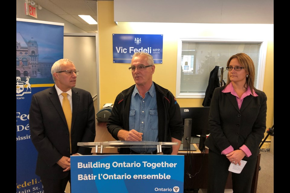 MPP Vic Fedeli, and Andy Mitchell, President, Unifor Local 103, and Corina Moore, President of Ontario Northland Transportation Commission, talk with reporters this morning. Photo Richard Coffin.