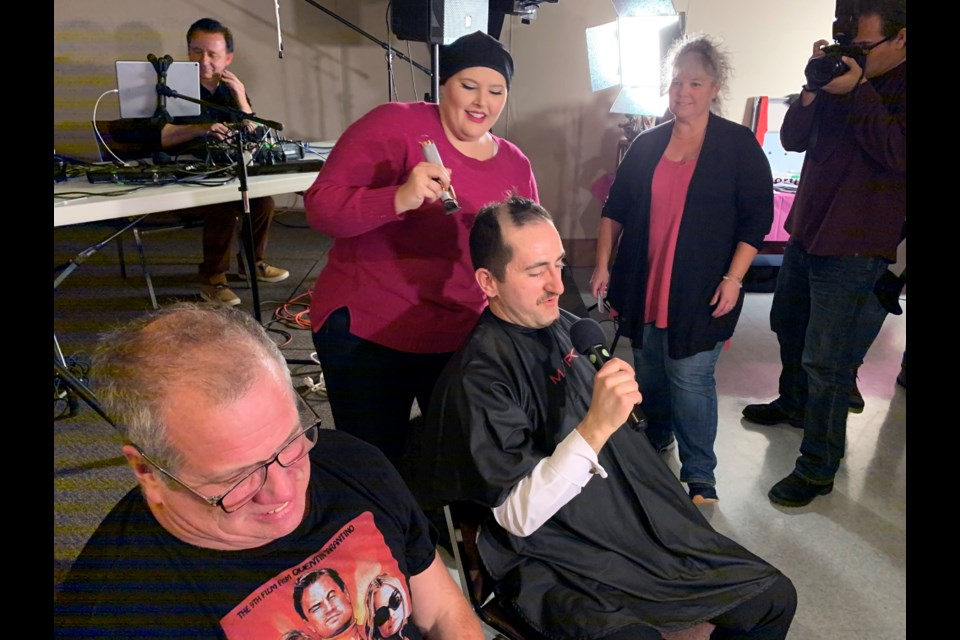 CTV reporter Brittany Bortolon prepares to make the first pass with hair clippers on Cogeco's Clarke Heipel while fellow reporter Greg Estabrooks nervously awaits his turn. Chris Dawson/BayToday.