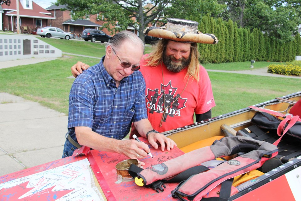 Legion Br. 23 Vice President Jim Thompson signs the canoe of Mike Ranta. The adventurer is crossing Canada to raise the issue of PTSD among veterans. Photo by Jeff Turl.